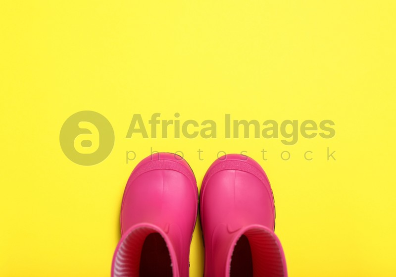 Pair of bright pink rubber boots on yellow background, top view. Space for text