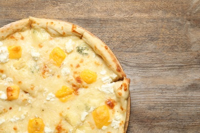 Hot cheese pizza Margherita on wooden background, top view. Space for text