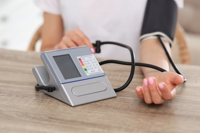 Woman checking blood pressure at wooden table indoors, closeup