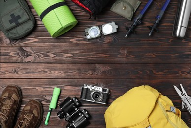 Flat lay composition with tourist backpack and camping equipment on wooden background, space for text