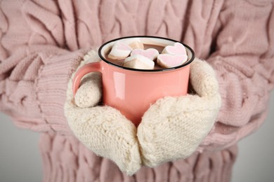 Woman in knitted mittens holding cup of delicious hot chocolate with marshmallows, closeup