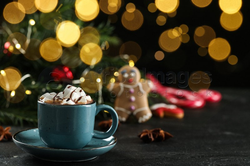Delicious hot chocolate with marshmallows and syrup on black table against blurred lights, space for text