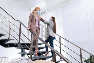 Office employees in masks greeting each other by bumping elbows on stairs