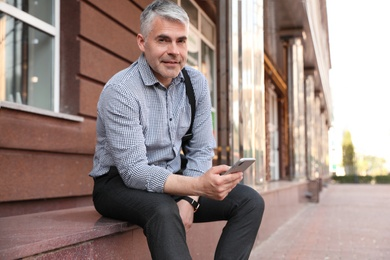 Portrait of handsome businessman with mobile phone in city, space for text