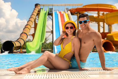 Happy couple near swimming pool at water park. Summer vacation
