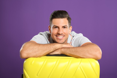 Handsome man with suitcase for summer trip on purple background. Vacation travel