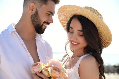 Happy young couple with flowers at beach near sea. Honeymoon trip