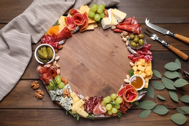 Assorted appetizers served on wooden table, flat lay. Space for text