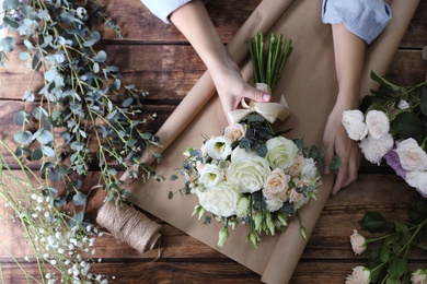 Florist wrapping beautiful wedding bouquet with paper at wooden table, top view