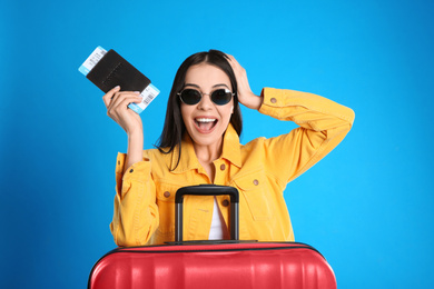 Beautiful excited woman with suitcase and ticket in passport for summer trip on blue background. Vacation travel