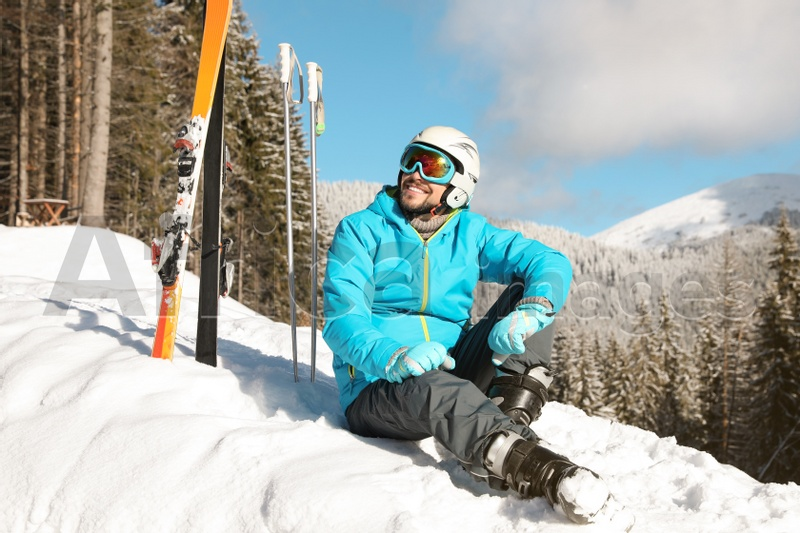 Man with ski equipment sitting on snow in mountains. Winter vacation
