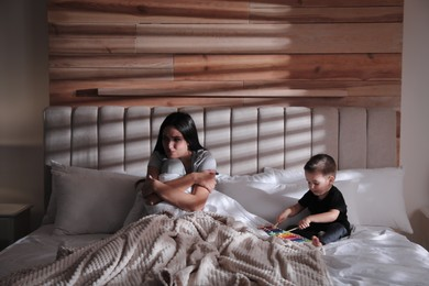 Depressed single mother with child in bed at home