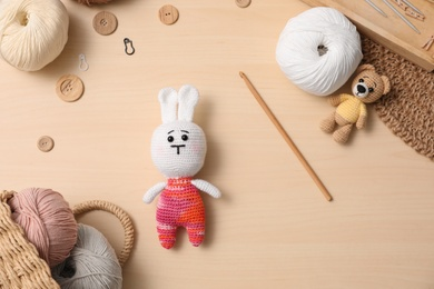 Flat lay composition with threads and crocheted toys on wooden table. Engaging hobby