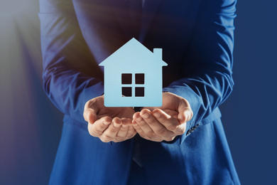 Home security concept. Man holding house on dark background, closeup