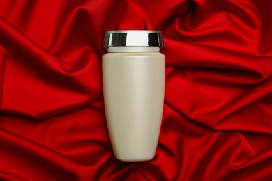Bottle of hair care cosmetic product on red fabric, top view