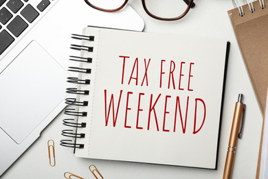 Notebook with text TAX FREE WEEKEND, laptop and pen on white table, flat lay