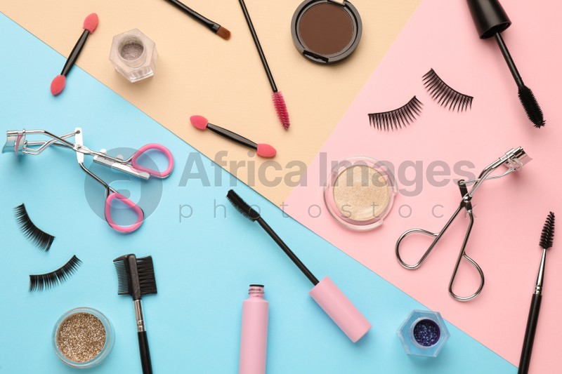 Flat lay composition with eyelash curler, makeup products and accessories on color background