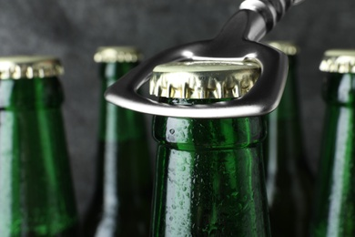 Opening bottle of tasty cold beer on grey background, closeup