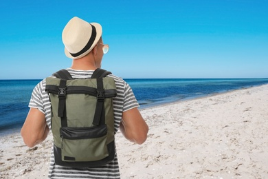 Traveler with backpack on sandy beach during summer vacation trip, back view. Space for text