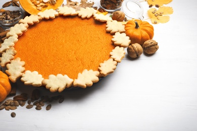 Delicious homemade pumpkin pie on white wooden table. Space for text