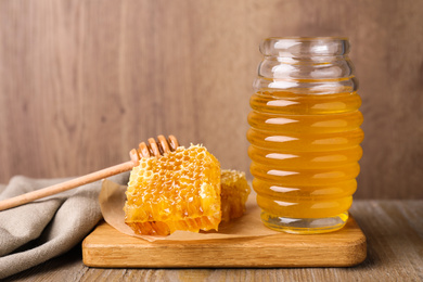 Jar of tasty aromatic honey and combs on wooden table