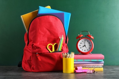 Backpack with school stationery on table against blackboard