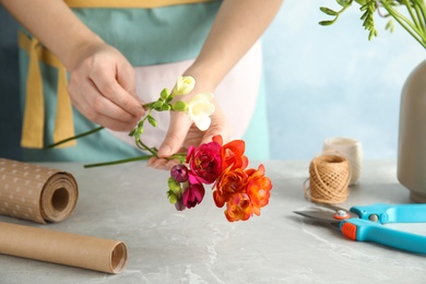 Woman making bouquet of freesia flowers at table, space for text