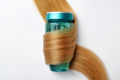 Bottle wrapped in lock of hair on white background, top view. Natural cosmetic product
