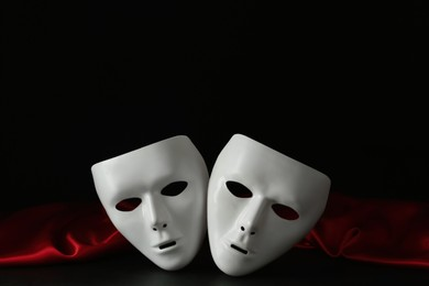 White theatre masks and red fabric on black background
