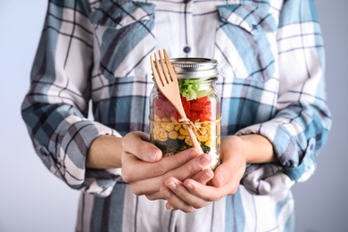 Woman holding glass jar with healthy meal, closeup