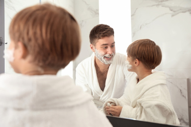 Dad and son with shaving foam on faces in bathroom