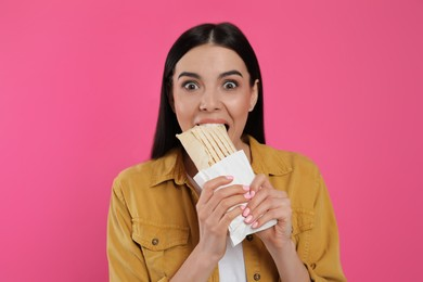 Emotional young woman eating delicious shawarma on pink background