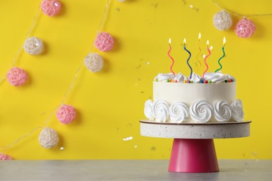 Birthday cake with burning candles on table near yellow wall, space for text