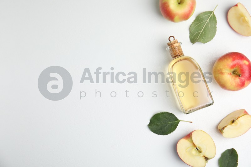 Natural apple vinegar and fresh fruits on white background, top view. Space for text