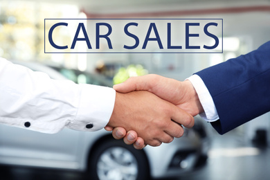 Young salesman shaking hands with client in car dealership, closeup