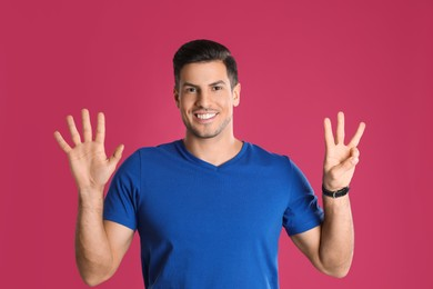 Man showing number eight with his hands on pink background