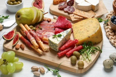 Set of different delicious appetizers served on white wooden table