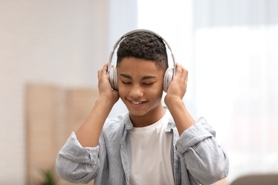 African-American teenage boy listening to music with headphones at home