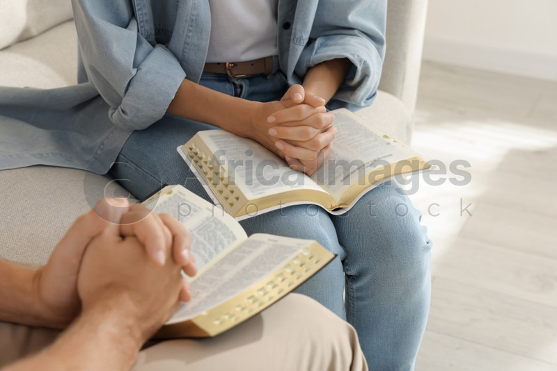 Religious people with Bibles praying together indoors, closeup