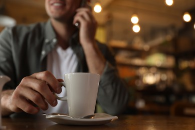 Man with cup of coffee talking on smartphone at cafe in morning, closeup. Space for text