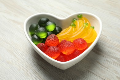 Delicious gummy fruit shaped candies on white wooden table