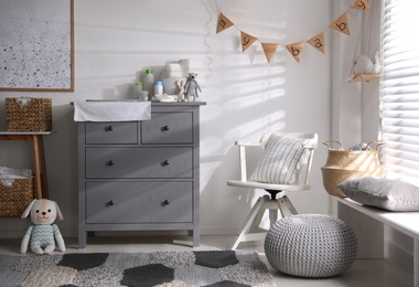 Chest of drawers with changing place in baby room. Interior design