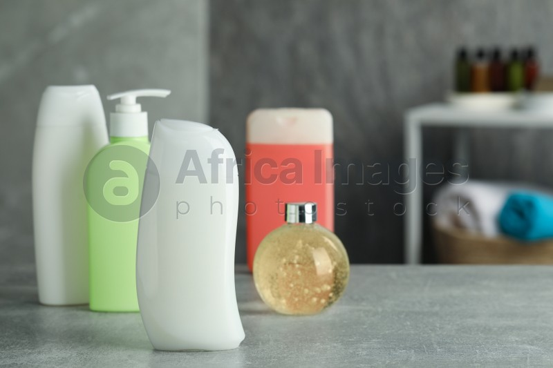 Bottles of shower gel on grey table in bathroom, space for text