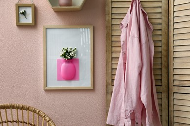Silicone vase with beautiful white flowers on pink wall in room