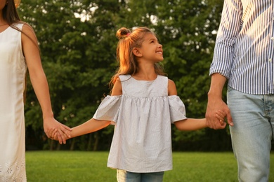 Little girl and her parents holding hands in park. Happy family