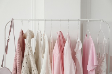 Rack with stylish clothes near white wall, closeup