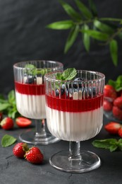 Delicious panna cotta with fruit coulis and fresh berries on dark grey table
