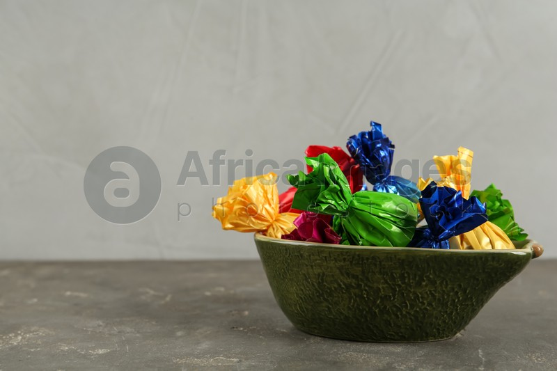 Candies in colorful wrappers on grey table, space for text
