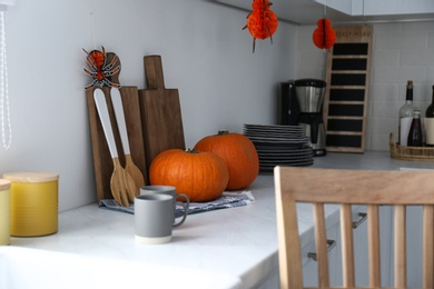 Fresh ripe pumpkins on countertop in kitchen decorated for Halloween