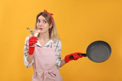 Young housewife with frying pan and glass of martini on yellow background